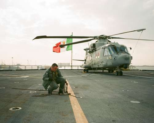 Flight deck crewman removes cable used to secure aircraft
