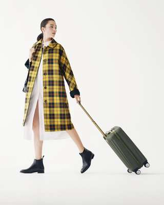 Coat by Mackintosh, dress by Priory, boots by Church's, bag by Smythson, suitcase by Piquadro