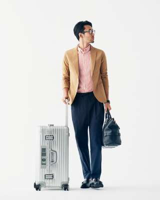 Jacket by Ships, shirt by Steven Alan, trousers by Undecorated Man, shoes by Paraboot, glasses by Ray-Ban, watch by Vacheron Constantin, suitcase by Rimowa, bag by Bally
