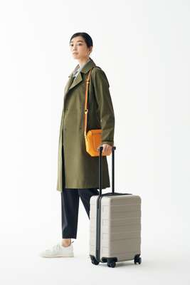 Coat by Arc'teryx, shirt by Gant, trousers by Barena, trainers by Golden Goose Deluxe Brand, bag by Hermès, suitcase by Muji