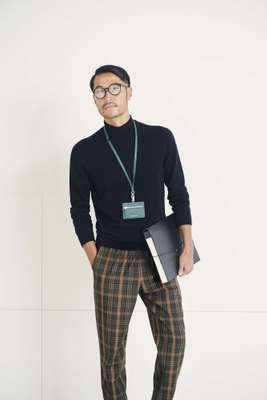 High-neck jumper by Bottega Veneta, trousers  by Barena Venezia, glasses by Ray-Ban, lanyard by Porter