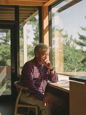 Canadian architect Ian MacDonald in his cabin home on the shore