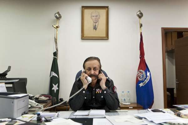 Waseem Ahmed, Karachi chief of police, talks on his landline and mobile phone in his office