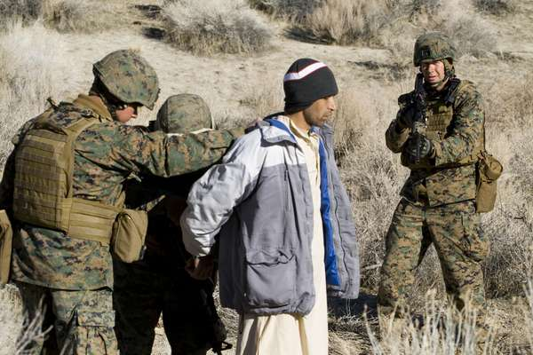 An Afghan 'villager' is searched by Marines and ANA role players
