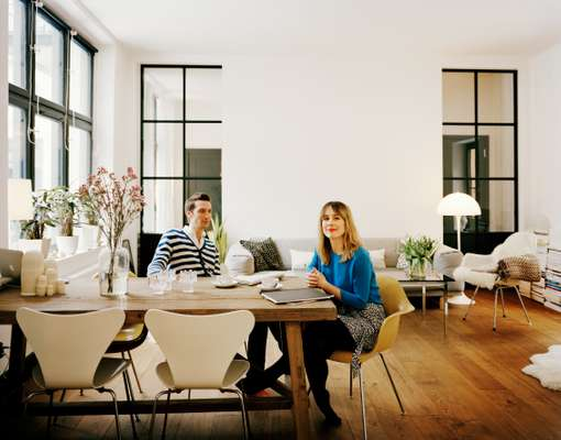 Carin Wester and Thomas Pouverel at their dining table with a mix of Jacobsen and Eames chairs