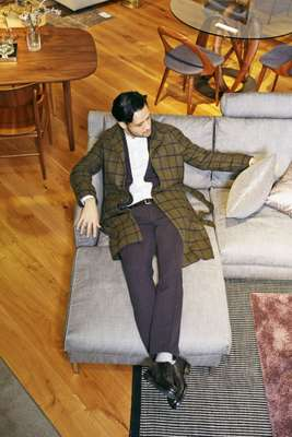 Coat by Stile Latino from Beams, jacket and trousers by Circolo 1901, shirt by United Arrows, socks by Tabio, shoes by Crockett & Jones, belt by APC, sofa by Eilersen