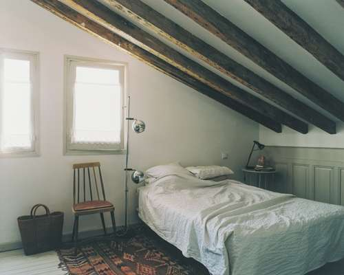 Airy wooden-beamed bedroom