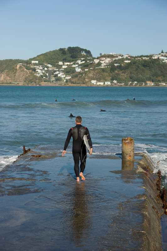 Surfers at Lyall Bay, 15 minutes from Wellington's CBD