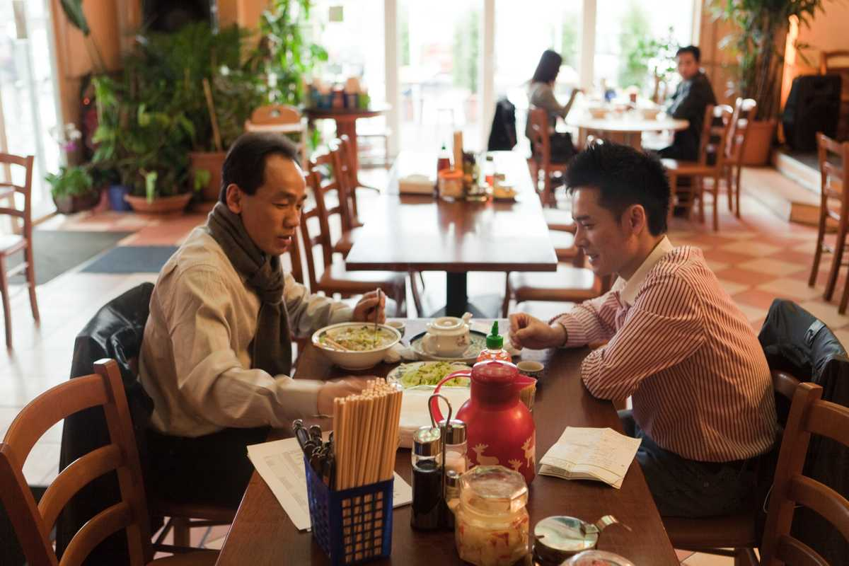 Nquyen Kien Coung (left), who runs a snack bar, and Cu Huu Viet, who works at a food market, have lunch at Dong Xuan Center