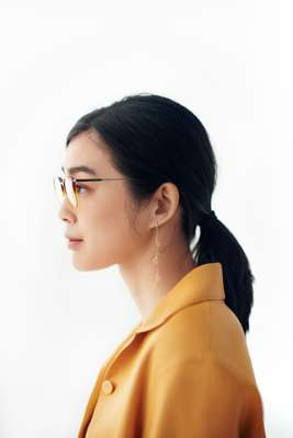 Jacket by Hermès, glasses by Prada, earring by Sarah & Sebastian
