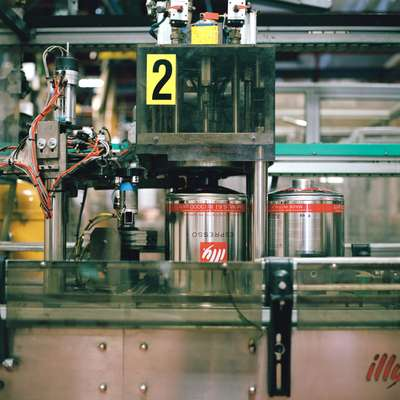 Illy's iconic red-striped tins move along the production line