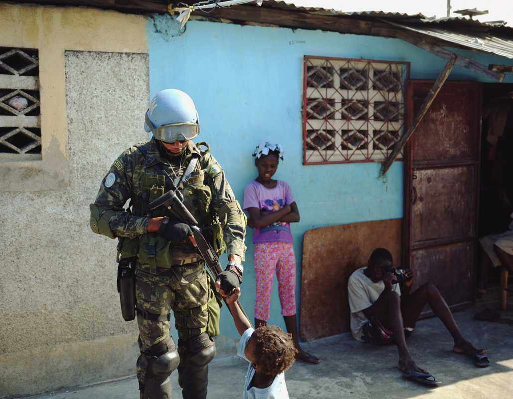 Brazilian soldiers bump fists with children in Cité Soleil