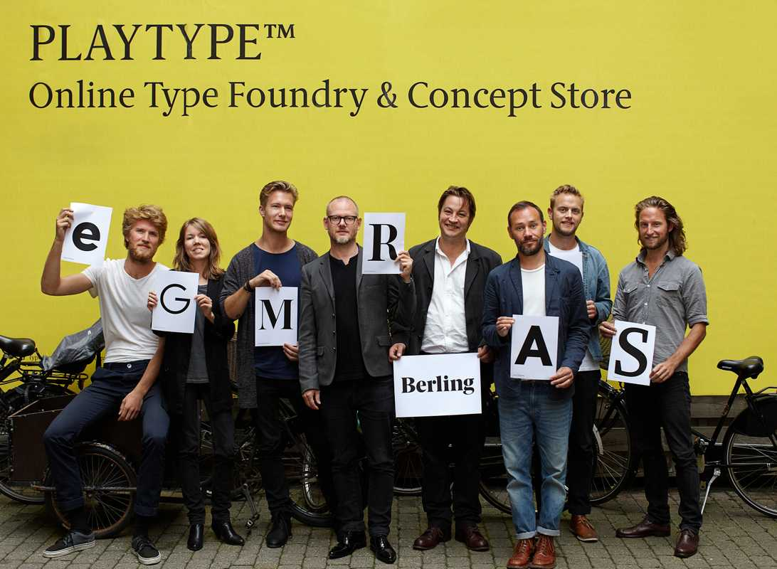 "E-Types staff holding printouts of their font designs, including creative director Jens Kajus (holding ""R"") and co-founder Jonas Hecksher (holding ""Berling"")"