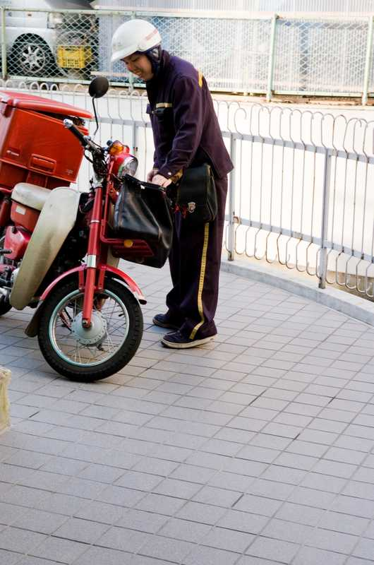 Postman with a Honda Super Cub. It's efficient on fuel, using 1 litre per 100km