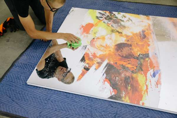 Worker readying a piece from the Korakrit Arunanondchai exhbition