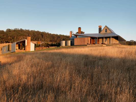 The Cottage and Shearing Quarters share the open grassland of a broad promontory overlooking Storm Bay
