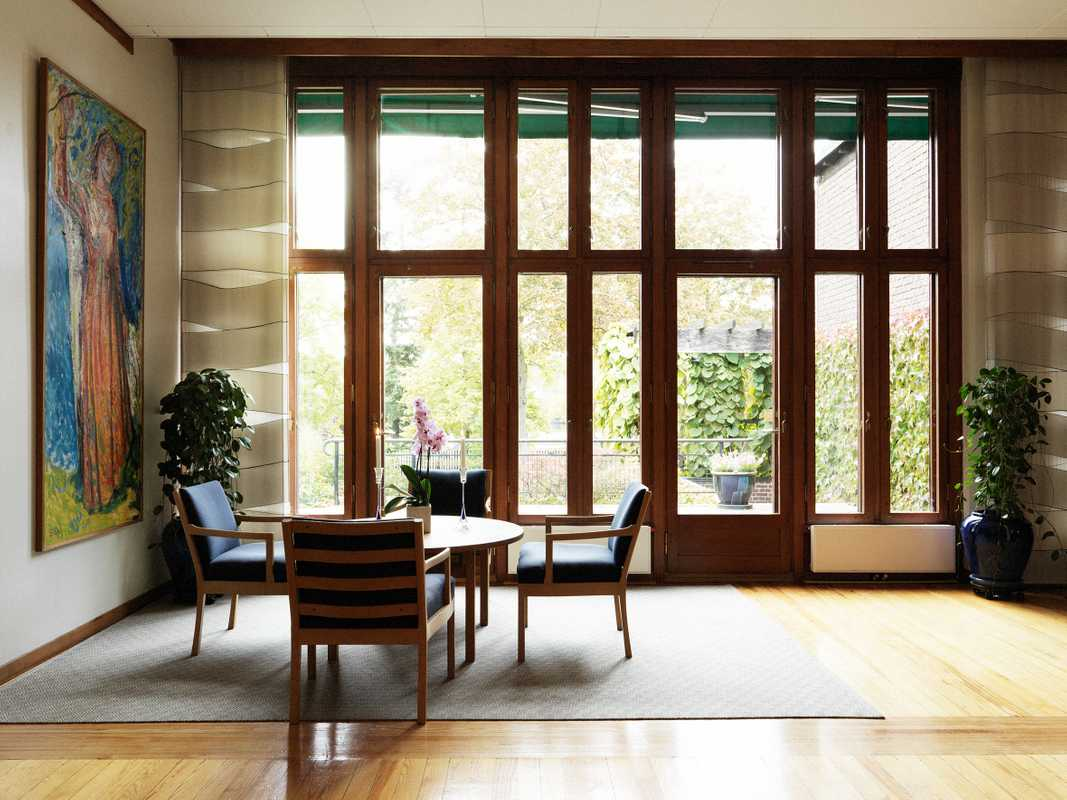 Teak-framed windows open out into the embassy garden