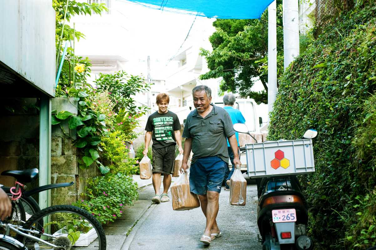 Craftsmen from Tsuboya pottery atelier, called Ikutouen, transporting materials to their atelier