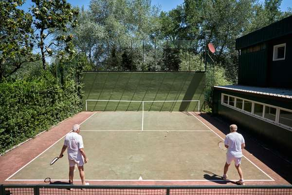 Members squeezing in a few sets at the practice tennis court