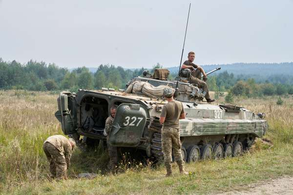 Ukrainian troops refill their vehicle while on a training mission