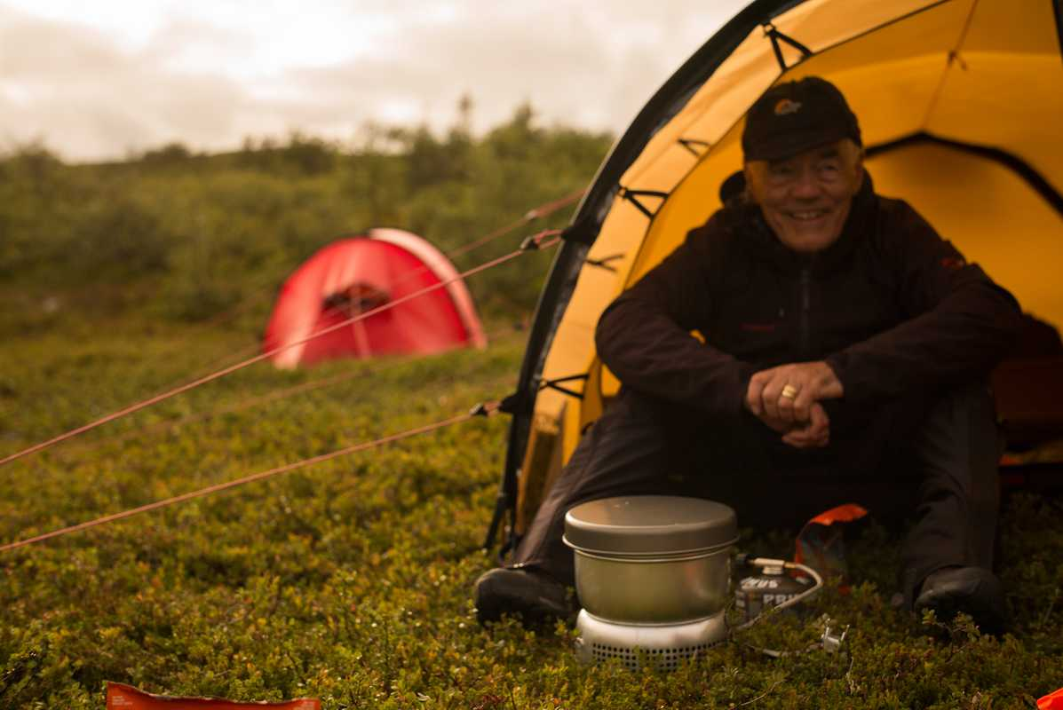 Hilleberg, sitting in  one of his tents with  a Trangia stove