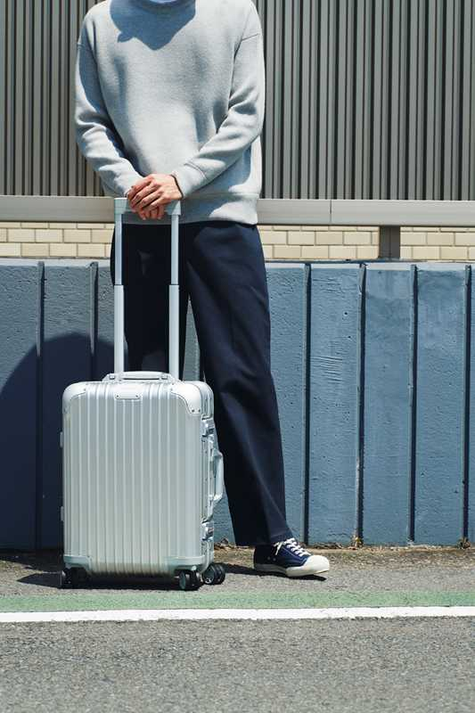 SWEATSHIRT by Studio Nicholson, TROUSERS by Make Sense Laboratory, TRAINERS by Moonstar, SUITCASE by Rimowa