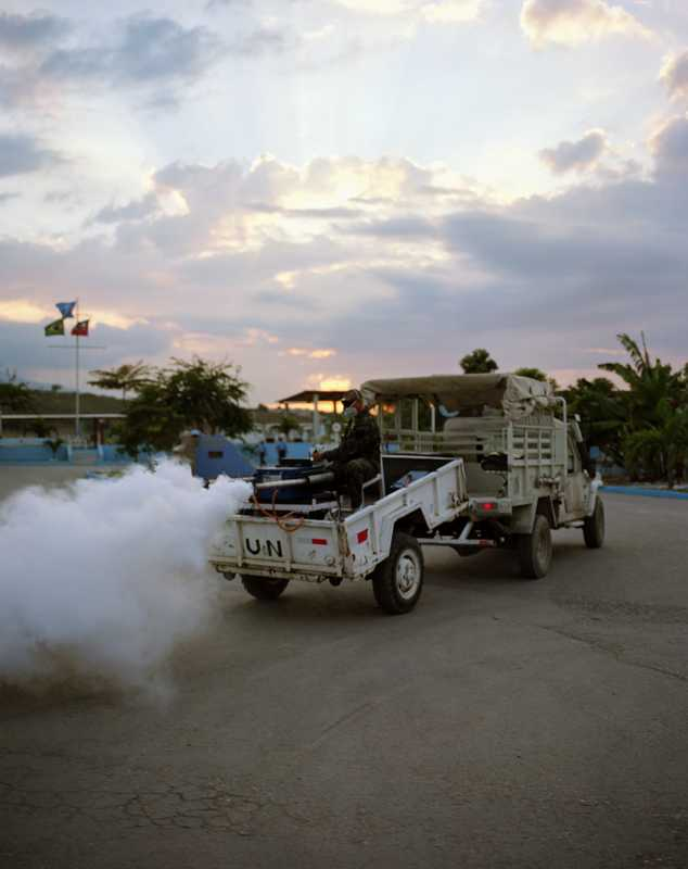 An anti-malaria fumigation team sprays General Barcellar Camp