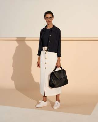 Jacket by Maison Kitsuné, pullover by Norse Projects,  skirt by Bella Freud, trainers by Santoni, glasses by Lindberg,  bag by Salvatore Ferragamo