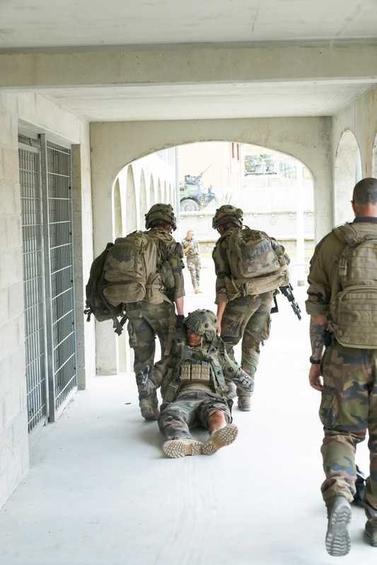 An injured soldier being dragged to safety in a training battle