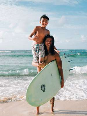 Surf instructor showing  a young pupil how to stay  on top of the waves