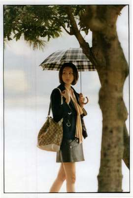 Jacket, skirt, bag by Louis Vuitton, blouse by Chloé, umbrella by Traditional Weatherwear, earrings by Duna