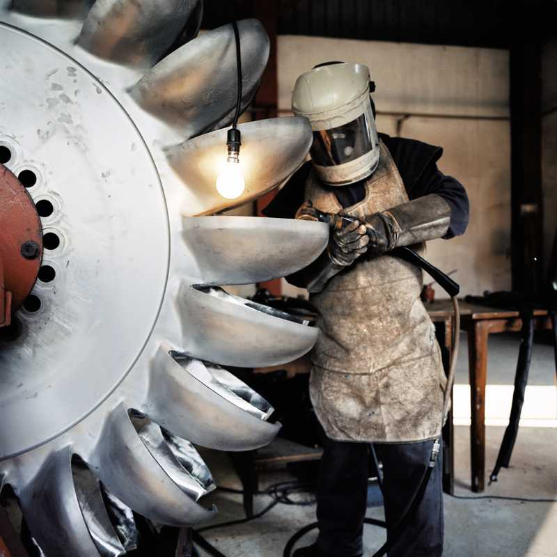 Engineer at the Khimti hydro plant works on one of its two-tonne steel turbines