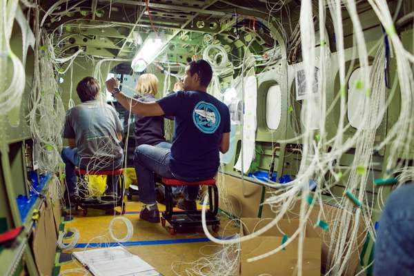 Viking Air employees stringing wires through the chassis of a Twin Otter