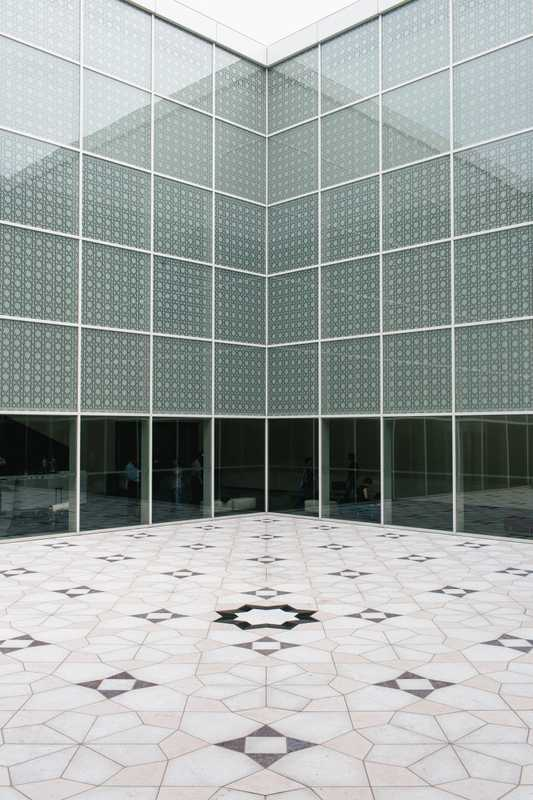 Interior courtyard where the windows and floor are adorned with geometric 'mashrabiya' patterns