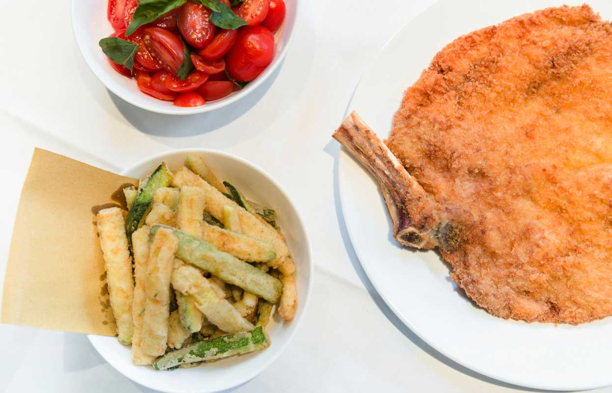 Veal Milanese with sides of tomatoes and 'zucchini fritti'