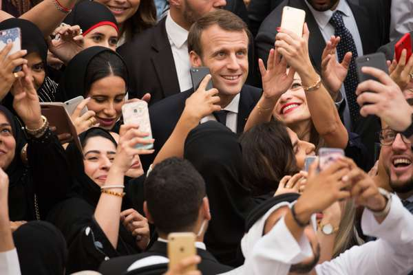 A mobbed Macron steps off the red carpet