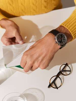 JUMPER by Lardini, GLASSES by Lindberg,  ARCEAU WATCH by Hermès, ENVELOPE and CARD by  Smythson