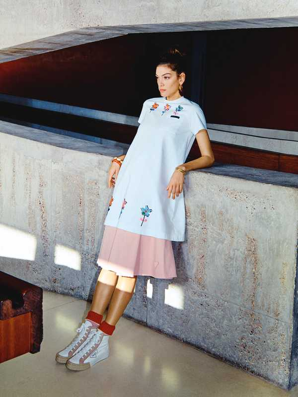 T-shirt dress, skirt, trainers and  socks by Prada, earrings by Patou, bracelets by Saint Laurent