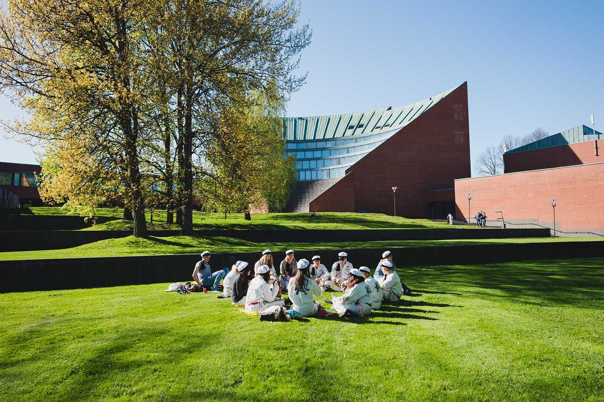 Students sitting outside Aalto University in Otaniemi, Espoo