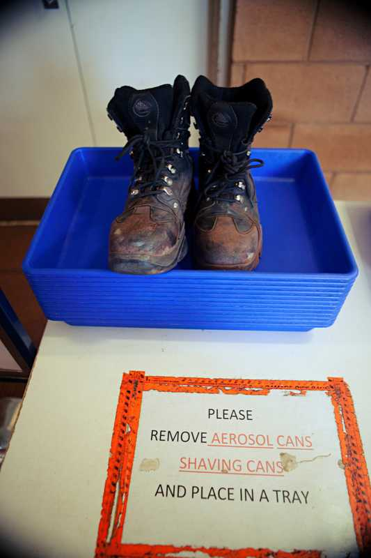 Steel-capped work boots wait to be scanned at the security check, Karratha Airport