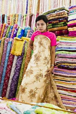Vendor modelling fabric for wedding dress in stall at Scott Market