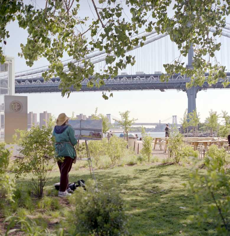 A pastoral painting scene in the Brooklyn Bridge Park