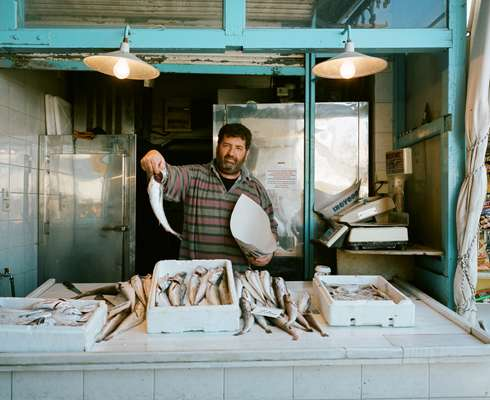 Vendor showing off his produce at Aegina's main fish market