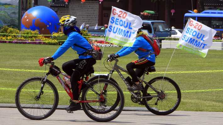 Volunteers on bicycles carry G20 banners
