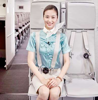 A flight attendant takes her jumpseat