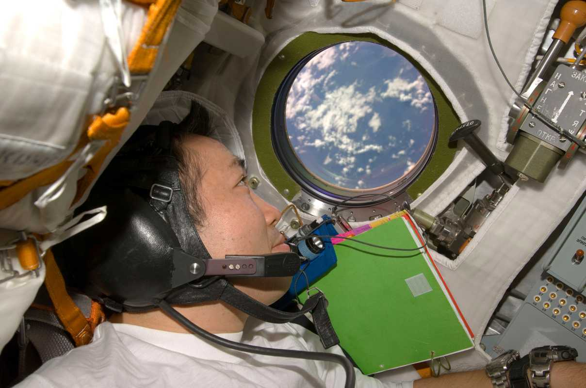 Wakata looks through the window on board the Soyuz TMA-14 spacecraft