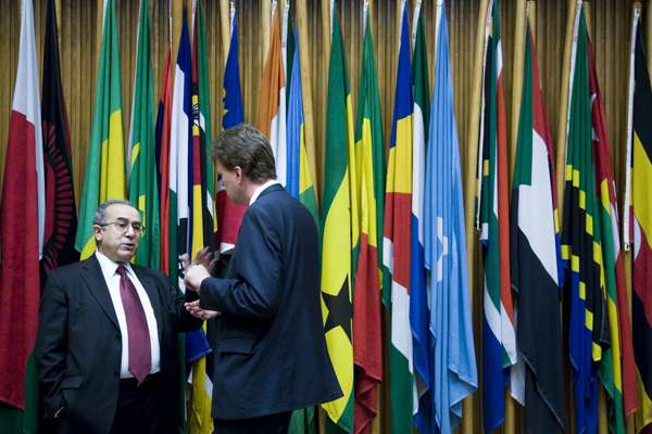 Visitors stand in front of the flags of member states in the AU headquarters