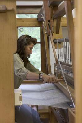 Emy Maguet works on a loom
