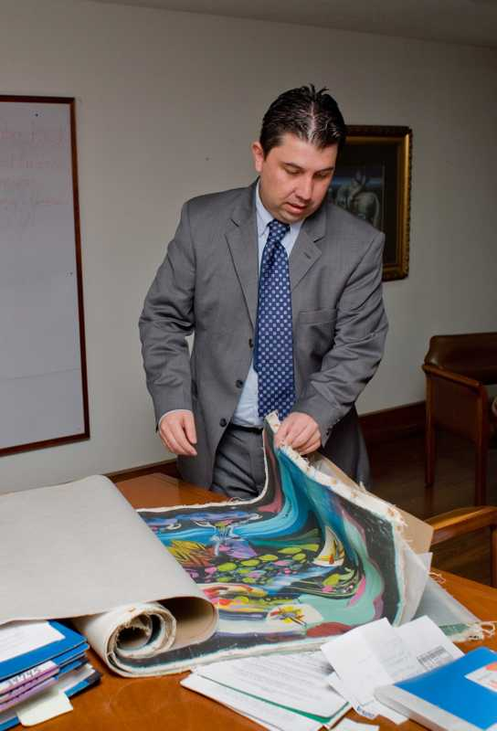 DNE investigator views confiscated paintings by well-known Colombian artist Alejandro Obregon ahead of their auction