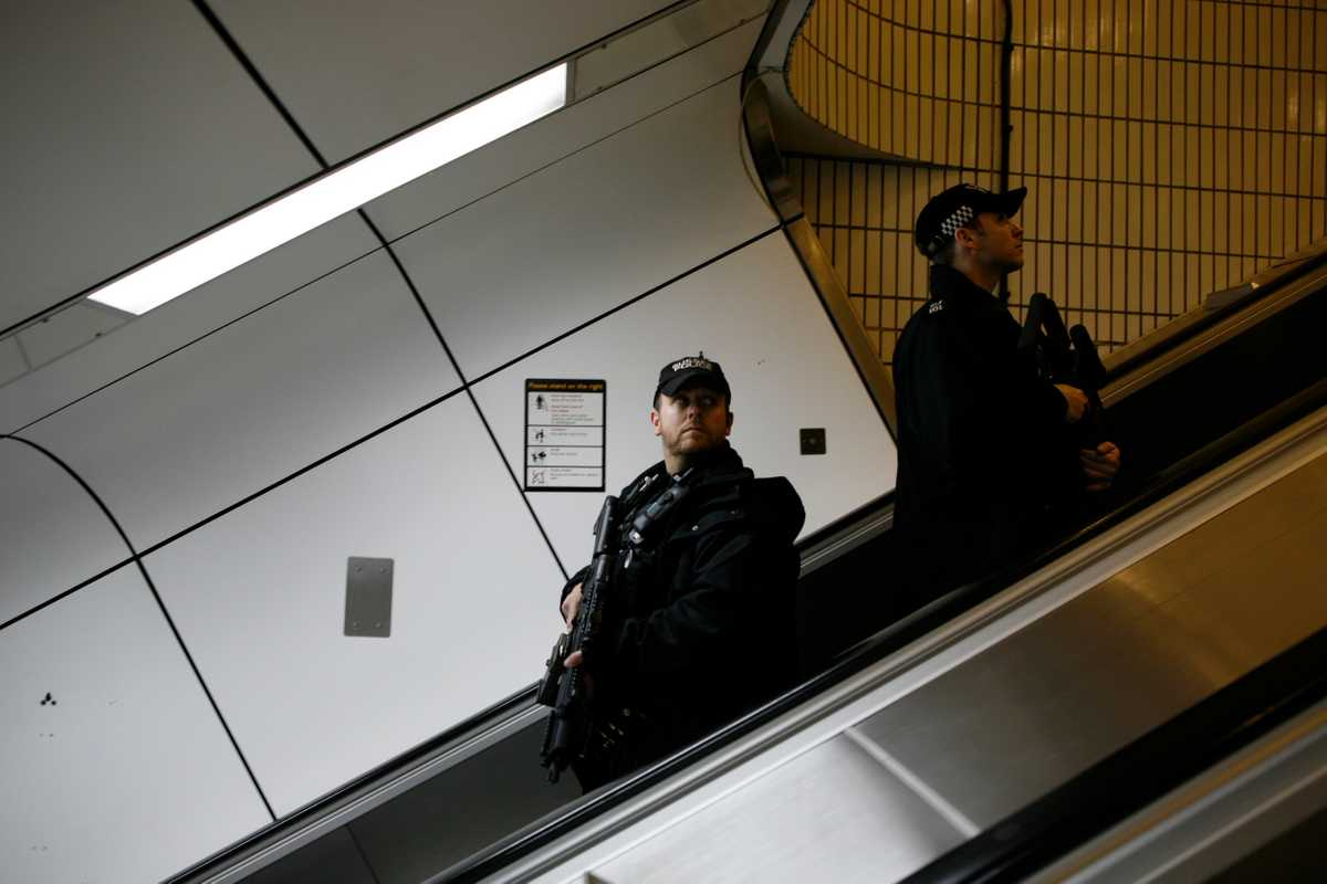 Firearms officers ascend an escalator from Gatwick station to the airport